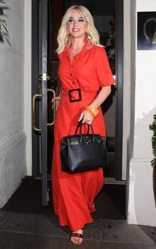 Katy Perry într-o rochie cămașă lungă, roșie, marcată în talie cu o curea de aceeași culoare și cu o cataramă neagră. Katy Perry, la întâlnire cu logodnicul ei, Orlando Bloom
