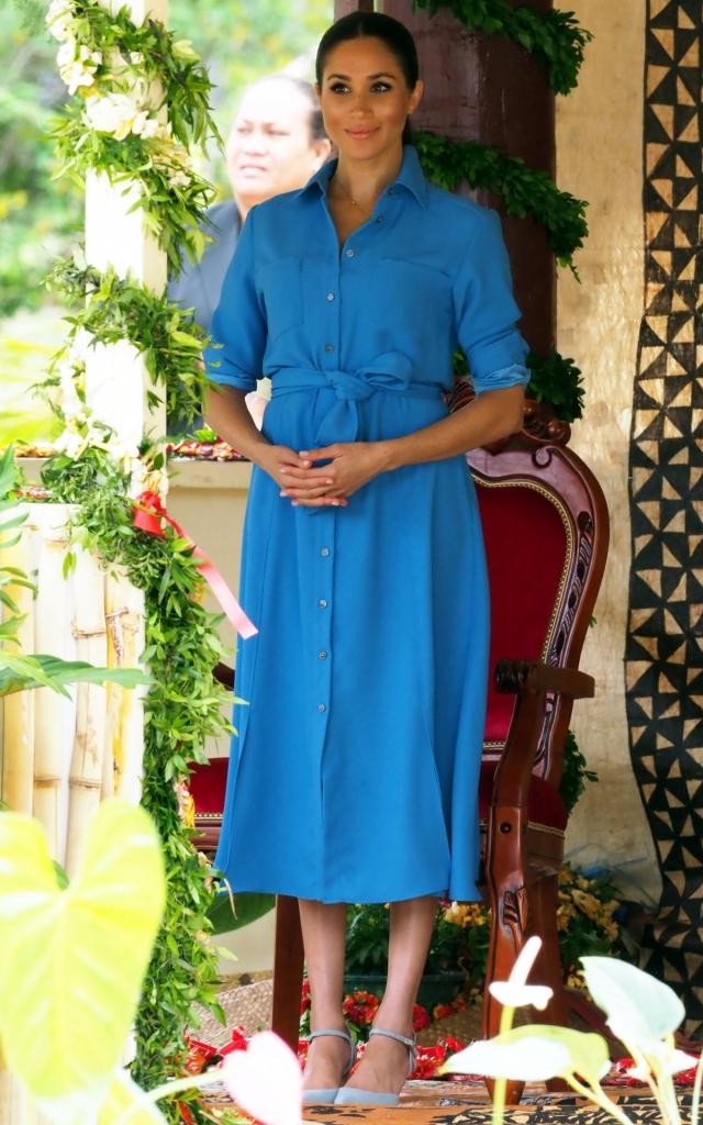 Meghan Markle într-o rochie cămașă albastră, peste genunchi, marcată în talie cu un cordon. Meghan Markle în timpul primului ei turneu regal.