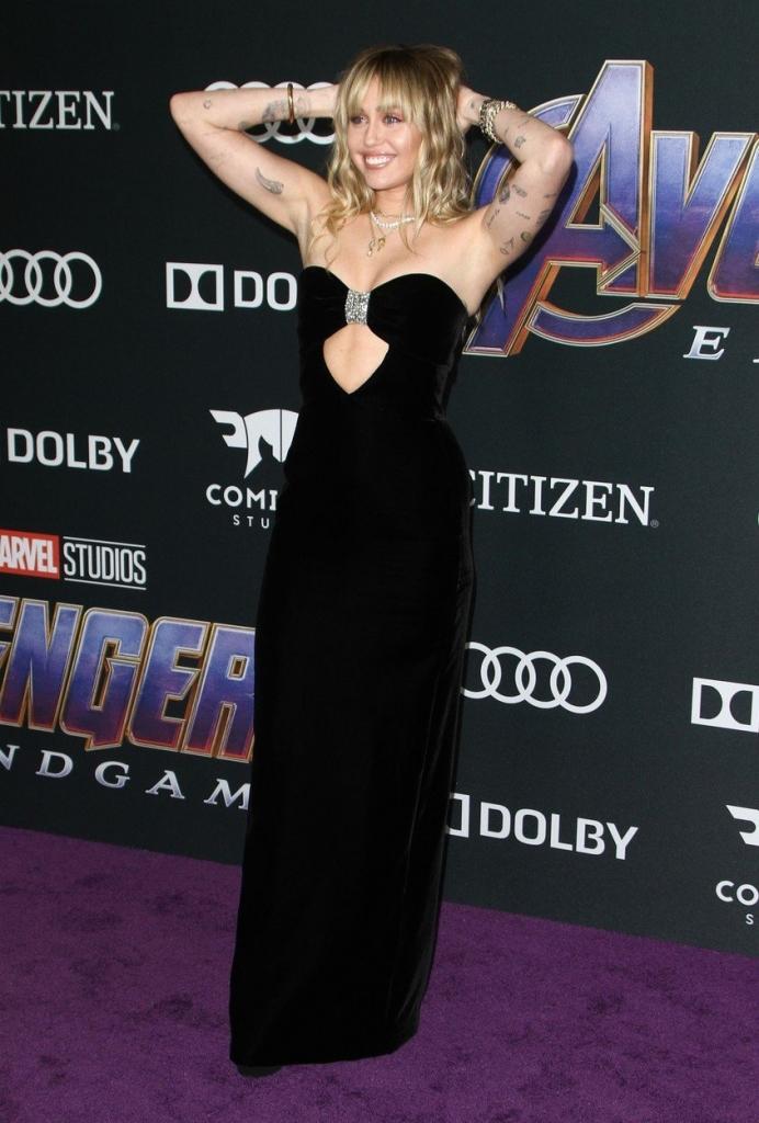 """Miley Cyrus la premiera internațională a filmului """"Avengers: Endgame"""", într-o rochie neagră, fără bretele, creație Yves Saint Laurent."""