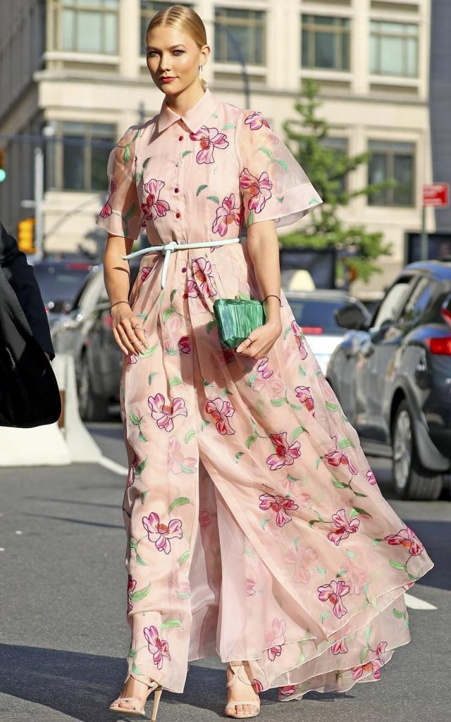 Modelul Victoria's Secret Karlie Kloss, într-o rochie maxi roz pudrat cu imprimeu floral, accesorizată cu un clutch turcoaz și sandale nude la Premiile FiFi