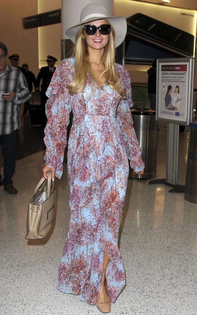 Paris Hilton, într-o rochie maxi bleu deschis cu impreumeu floral și mâneci cu volane, accesorizată cu poșetă, pălărie și ochlari de soare.